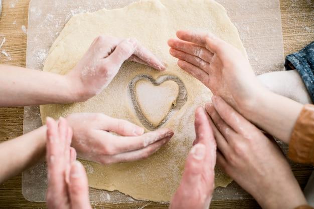 Варить и домашняя концепция - близкие вверх женских рук делая печенья от свежего теста дома. руки трех женщин держат печенье в форме сердца Premium Фотографии