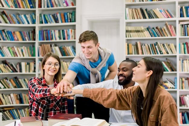 図書館に一緒に座って、団結とチームワークを象徴する互いの上に手を置く多民族大学生 Premium写真