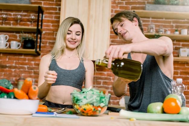 Диета, здоровое питание, фитнес-образ жизни, правильное питание. заботящаяся о здоровье пара готовит низкокалорийный ужин в домашней кухне. мужчина наливает в салат оливковое масло Premium Фотографии