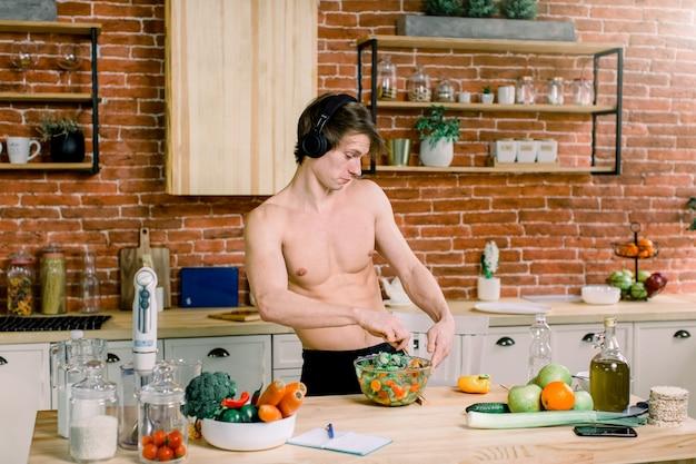 幸せなハンサムな男は、自宅のキッチンで料理をして、ヘッドフォンやダンスで音楽を聴きます。 Premium写真
