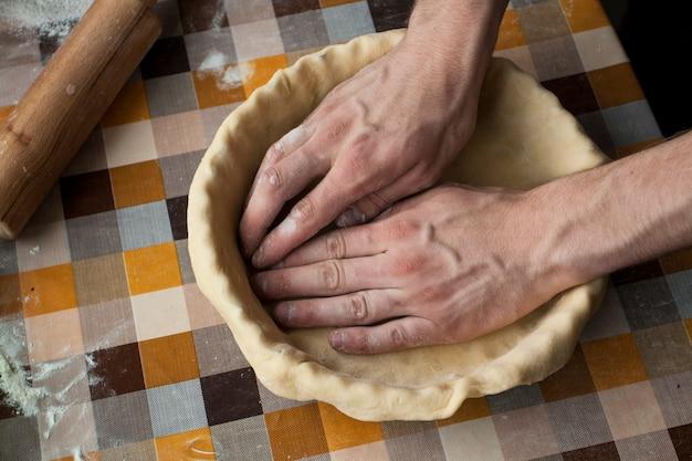 Крупным планом мужской руки замешивать тесто на поверхности в клетке Premium Фотографии