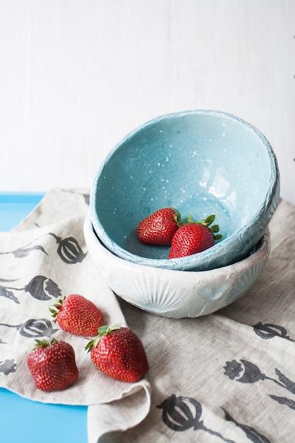 Синие ромашки с красной сочной клубникой на синем дереве Premium Фотографии