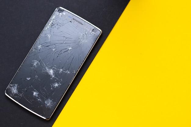 黄色と黒の背景に壊れた携帯電話。事故を表す壊れた画面を備えたデバイスの粉砕。 Premium写真