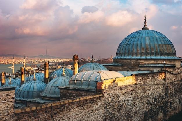 日没、イスタンブール、トルコのゴールデンホーンの美しい景色。イスタンブールの青い海に沈む夕日の光線でスレイマニエモスクの屋根 Premium写真