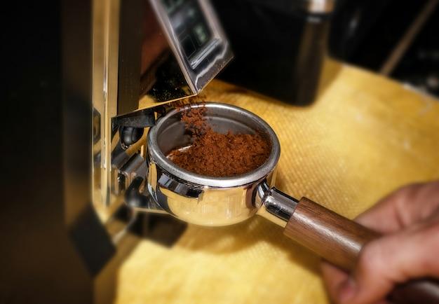 プロのグラインダーマシンでコーヒーを粉砕するマクロ撮影 Premium写真