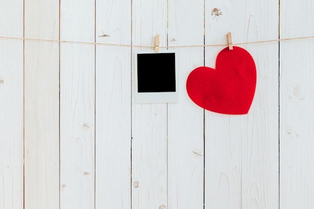 空の木製の白い背景に、洗濯物でぶら下がっている赤いハートとフォトフレームブランク。バレンタインデー。 Premium写真