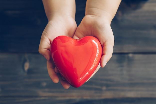 Крупным планом детей руки, давая красное сердце на фоне дерева Premium Фотографии