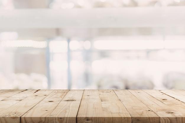 空の木製テーブルと背景をぼかした写真 - ショッピングモールの店は、製品の表示モンタージュと背景のボケ味をぼかし。 Premium写真