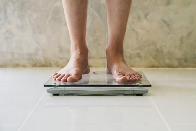 床、ダイエットの概念に体重計の男性。 Premium写真