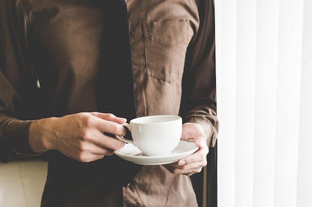 ウィンドウでコーヒーカップを保持している実業家。創造的なビジネスのスタートアップのアイデア。 Premium写真