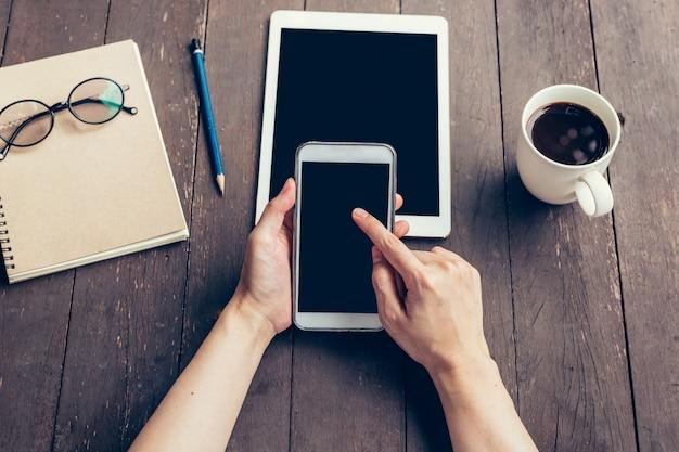 あなたの広告のための空白のコピースペース画面で電話を持っている女性の手を閉じます。コーヒーショップで電話を使用して手の女性。 Premium写真