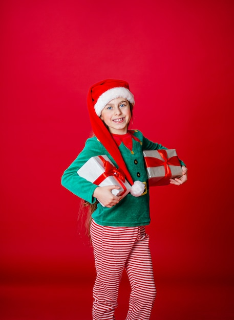 Счастливая девушка с подарками в костюме санта-клауса-помощника эльфа на ярко-красном Premium Фотографии