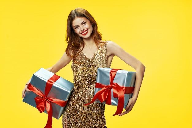 美しい服の色付きの背景のスタジオで彼女の手に贈り物の箱を持つ若い女性、贈り物、幸せなクリスマスと新年を販売 Premium写真