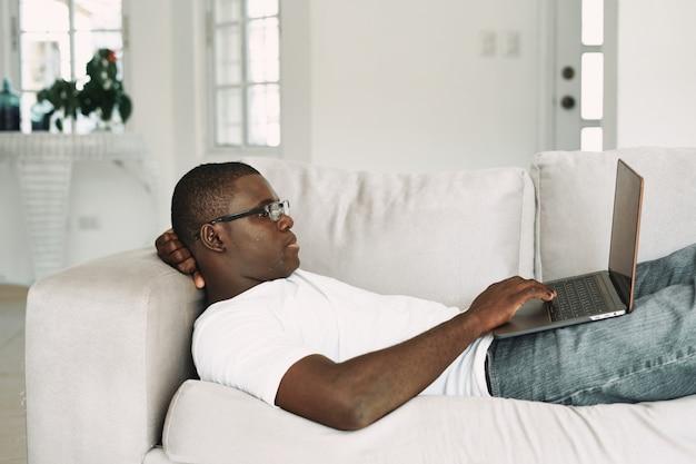 自宅で仕事をしているアフリカ系アメリカ人のフリーランサーのラップトップ Premium写真