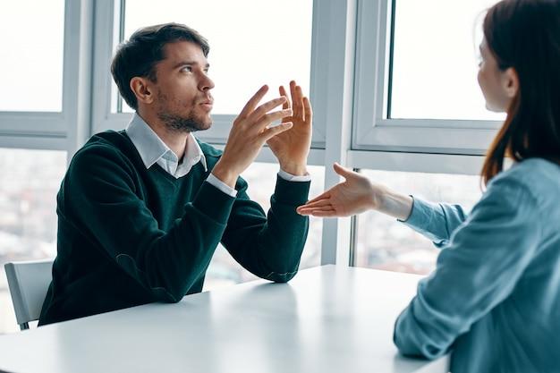 男と女がテーブルに座って話し、お互いに口論し、本当の口論、家事問題 Premium写真