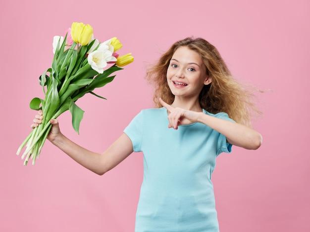 母の日、花でポーズをとる子供を持つ若い女性、女性の日と母の日への贈り物 Premium写真