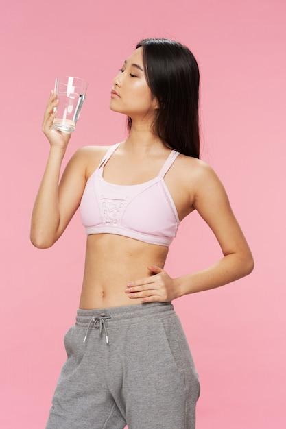 水のガラスを持つアクティブなアジアの女性 Premium写真