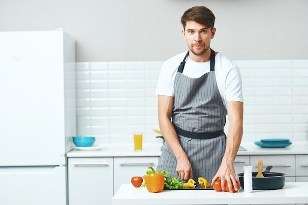 男性の料理人がキッチンで調理し、健康的な自家製料理 Premium写真