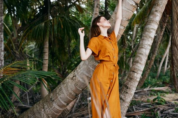 Женщина в желтом платье и шляпе идет вдоль океана по песку с пальмами Premium Фотографии