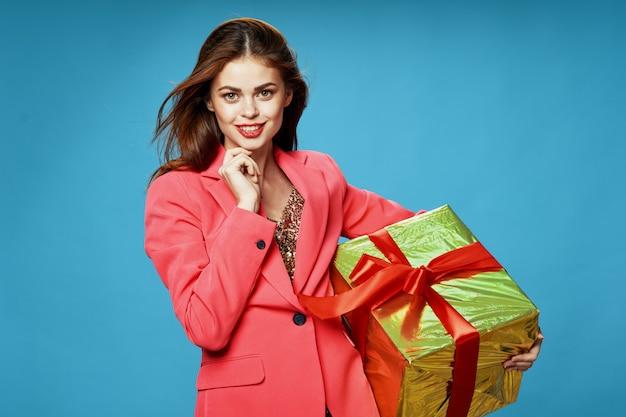 Молодая женщина с коробками подарков в руках на цветном фоне в красивой одежде, продажа подарков, счастливого рождества и нового года Premium Фотографии