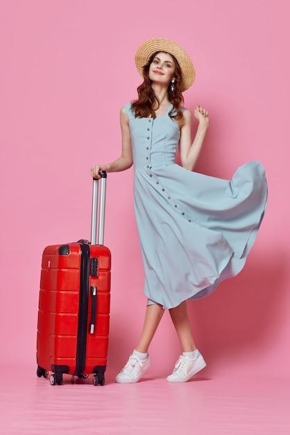 青いドレスの赤いスーツケースとファッション旅行女性 Premium写真