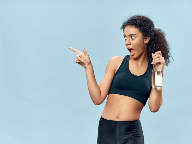 浅黒い肌のアフリカ系アメリカ人女性がトラックスーツでポーズをとって、スポーツをして Premium写真