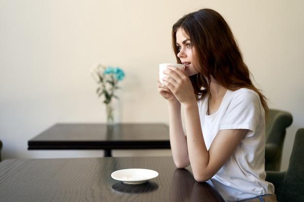 Женщина сидит в кафе, расслабляющий и пить кофе Premium Фотографии
