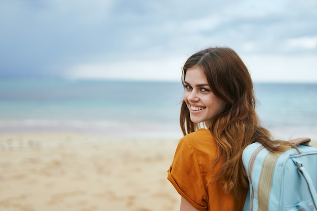 黄色のドレスを着た青いバックパックを持つ女性は、ヤシの木のある砂に沿って海に沿って歩く Premium写真