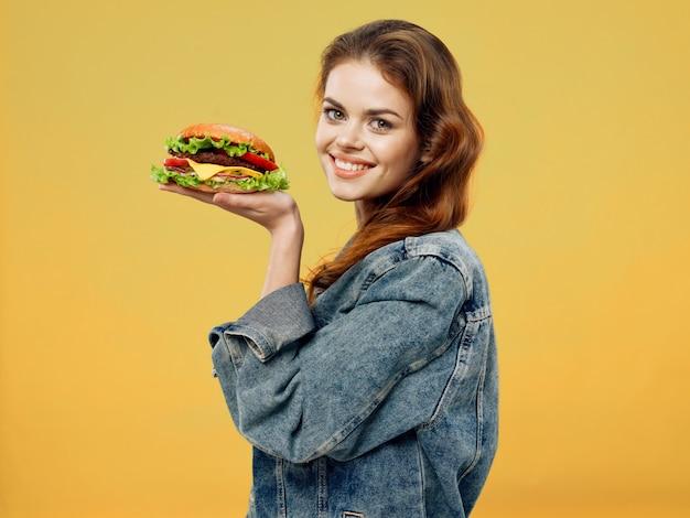 彼女の手でジューシーなハンバーガー、ハンバーガーを食べる女性と美しい若い女性 Premium写真