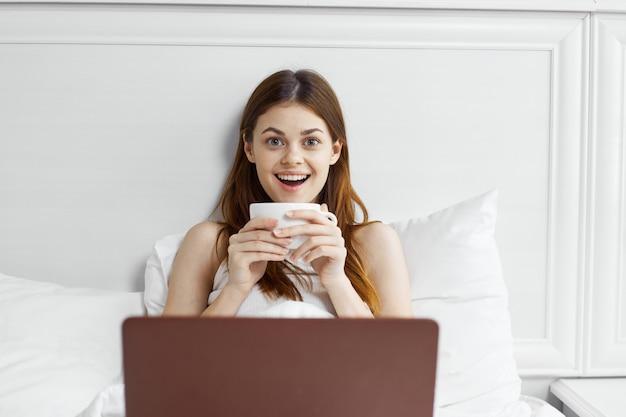 Женщина в постели с кружкой кофе и ноутбуком Premium Фотографии