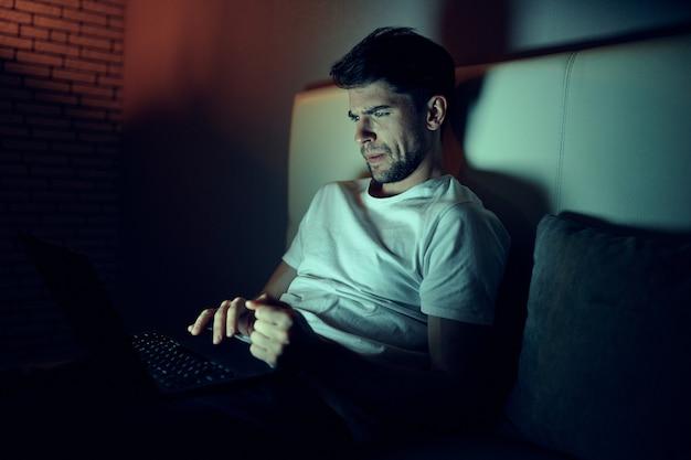 Мужчина работает на ноутбуке в постели, любимая женщина спит, ночная работа, измена Premium Фотографии