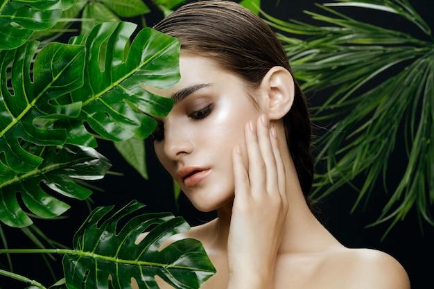 Красивый женский портрет в пальмовых кустах, красивая кожа лица Premium Фотографии