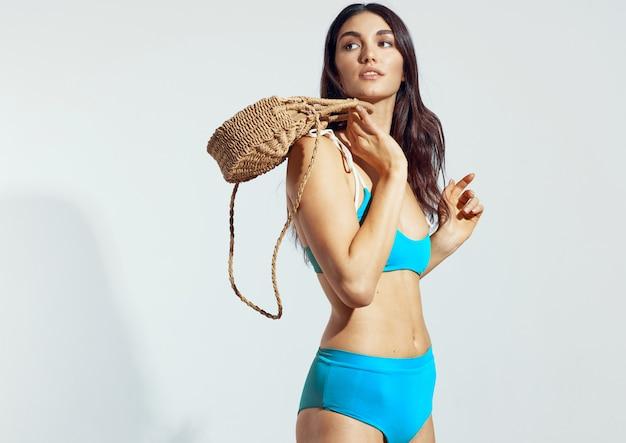 Молодая женщина в синем купальнике на светлом фоне. Premium Фотографии