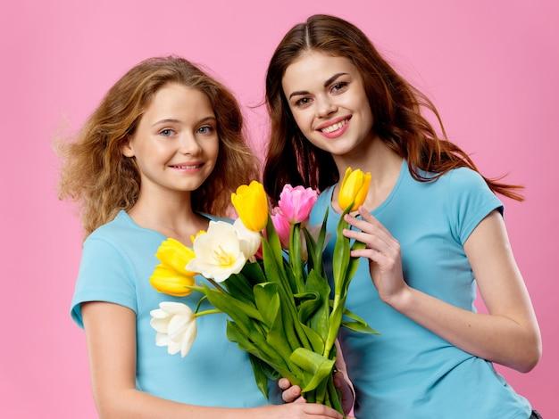 母の日、花とスタジオでポーズをとる子供を持つ若い女性、女性の日と母の日への贈り物 Premium写真
