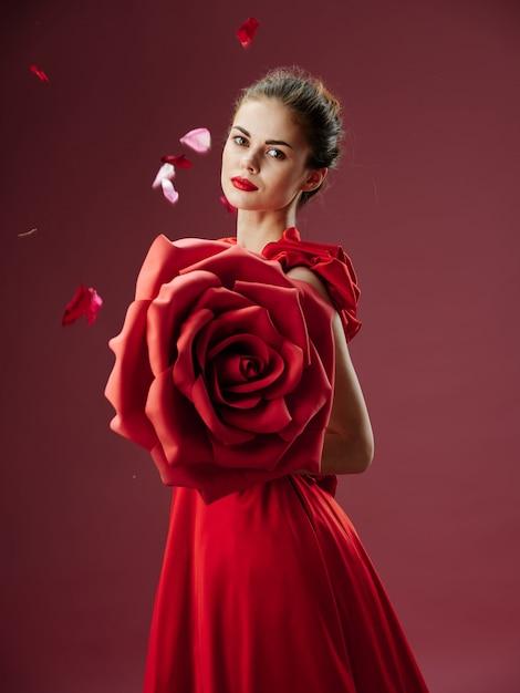 バラ、バラの花びら、スタイリッシュな画像、赤い口紅と豪華なドレスの美しい若い女性 Premium写真