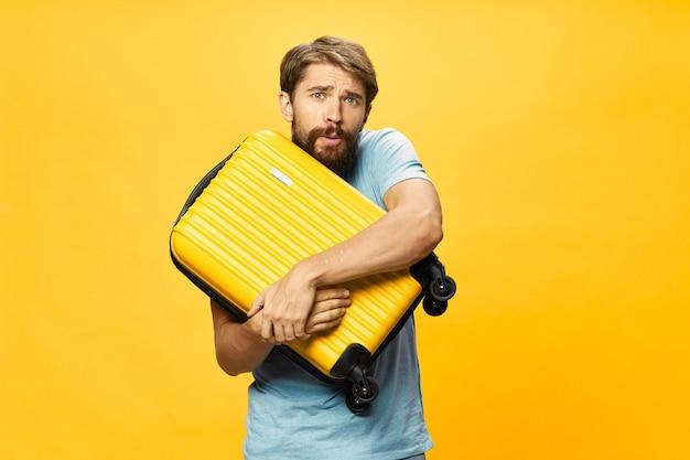 スタジオ、休暇でポーズをとって彼の手にスーツケースを持つ男性旅行者 Premium写真