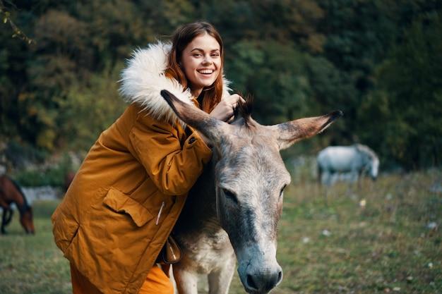 Женщина позирует с ослом на природе в горах Premium Фотографии