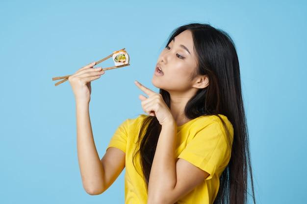 Красивая азиатская женщина ест суши с палочками Premium Фотографии
