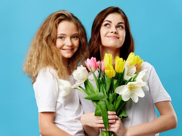 母の日、花のあるスタジオでポーズをとる子供を持つ若い女性、女性の日と母の日への贈り物 Premium写真