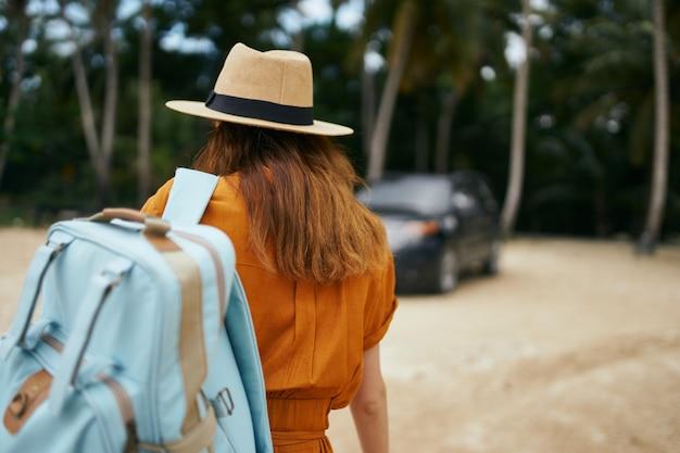 Женщина с синим рюкзаком в желтом платье и шляпе идет по океану по песку с пальмами Premium Фотографии
