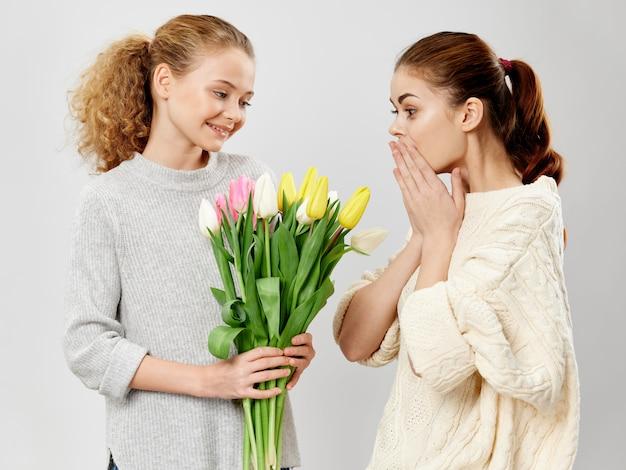 母の日、花を持つポーズをとる子供を持つ若い女性、女性の日と母の日への贈り物 Premium写真