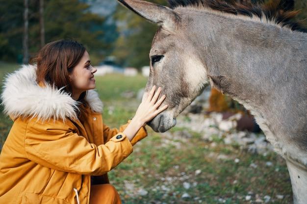 Женщина позирует с ослом на природе космических гор Premium Фотографии