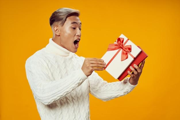 Возбужденный азиатский мужчина с подарочной коробкой Premium Фотографии