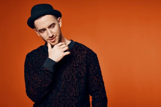 Человек в шляпе на красном фоне Premium Фотографии