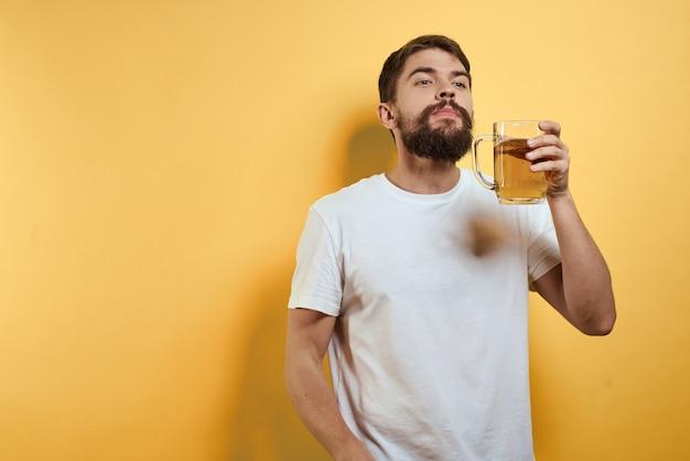 グラスからビールを飲み、ジャンクフライファーストフードを食べる男性 Premium写真