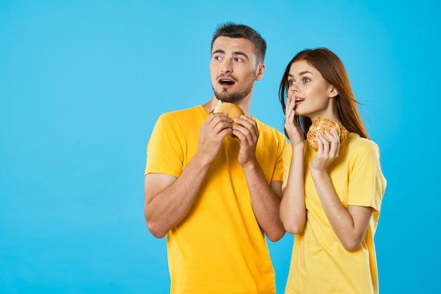Мужчина и женщина в ярких цветных футболках позируют вместе, пара Premium Фотографии