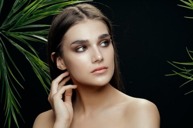 ヤシの茂み、顔の美しい肌の美しい女性の肖像画 Premium写真