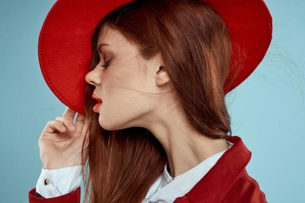 Красивая рыжеволосая женщина в деловом костюме и красной шляпе, стильный офисный образ Premium Фотографии