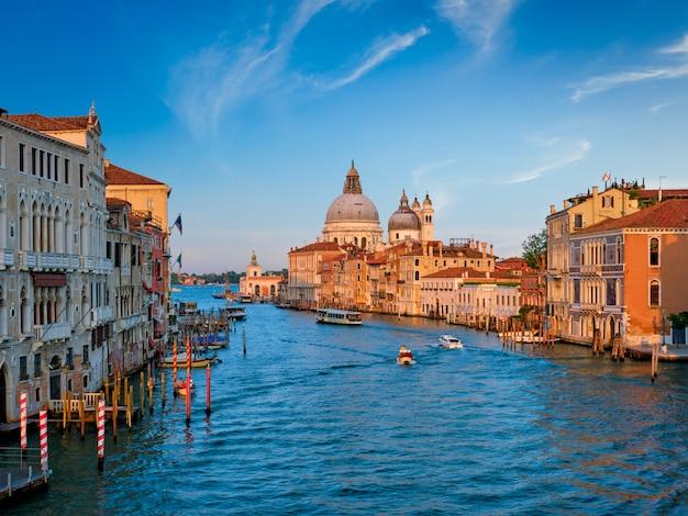 ヴェネツィア大運河と日没のサンタマリアデッラサルート教会のパノラマ Premium写真