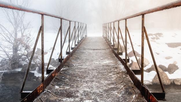 Небольшой металлический мост через ручей, выходящий в туман. Premium Фотографии